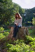 Young Sad Melancholic Woman Sit On Big Stub