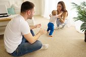 Baby Boy Doing First Steps With Parents Support. Baby Boy Doing First Steps. Mom, Dad And Toddler So poster