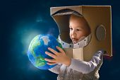 Child is dressed in an astronaut costume. Kid with globe. Earth day. poster