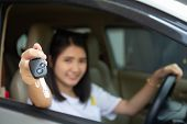Asian Car Driver Woman Smiling Showing New Car Key. Happy Young Girl Owner Taking Car Key From Deale poster