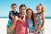 Portrait of happy family looking at camera at beach. Cheerful mother and father with cute daughter a poster