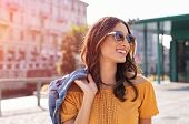 Happy latin woman walking on the street on a bright sunny day. Cheerful stylish girl with sunglasses poster