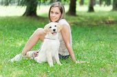 Young woman playing with her golden retriever puppy outdoors poster