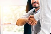 Close-up Of Two Businessmen Shaking Hands Together In Indoor Office Environment - Business Greeting, poster