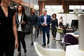Businesspeople Arriving For Work In Busy Modern Open Plan Office poster