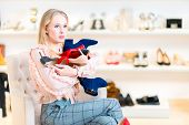 Shopping. Shoe Store. A Girl In Front Of A Choice: What Shoes To Buy? Holds Several Pairs Of Shoes poster