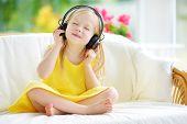 Cute Little Girl Wearing Huge Wireless Headphones. Pretty Child Listening To The Music. Schoolgirl H poster