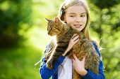 Cute Little Girl With Her Cat On Sunny Autumn Day. Adorable Child Holding Het Pet Kitty. poster