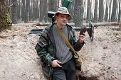 Military archeology. Man with metal detector and Soviet 82-mm mortar shell remains on the battlefield of WW2.