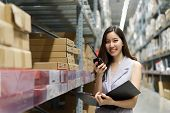 Smart Smiling Young Asian Woman Working In Store Warehouse. She Is Standing And Holding Document Fol poster