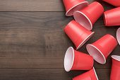Disposable Plastic Cups On The Wooden Background. Top View Of Used Plastic Cups. Red Plastic Cups On poster