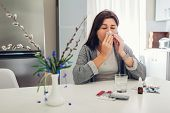 Spring Allergy. Young Woman Sneezing Because Of Flowers Surrounded With Pills On Kitchen. Seasonal A poster