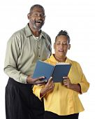 A happy senior African American couple sing a duet from the same book.  On a white background.