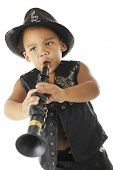 An adorable, intense preschool clarinetist in a sparkly fedora and black leather vest.  On a white b