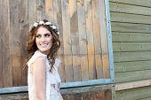 stock photo of bohemian  - Beautiful young bride is smiling with flowers in her hair outdoors - JPG