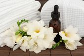 Freesia flower arrangement with aromatherapy essential oil bottle with white spa towels and linen sponge over bamboo background.
