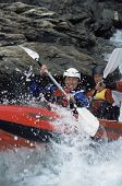 Men Rafting Down Fast Waters