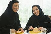 Middle Eastern Women Sat At Table Eating Food