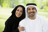 Middle Eastern Couple Sat On Grass In Park