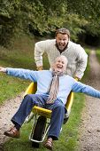 Man Pushing Father In Wheelbarrow