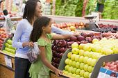 picture of department store  - Woman and daughter shopping for apples at a grocery store - JPG