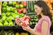 pic of grocery store  - Woman shopping for bell peppers at a grocery store - JPG