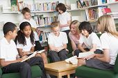 stock photo of tweenie  - Seven students in library reading books with teacher - JPG