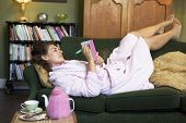 picture of housecoat  - Young woman lying on sofa at home writing in her diary - JPG