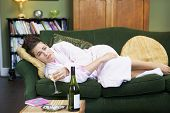 Woman Looking Sad On Sofa With Wine In Hand