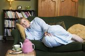 picture of saddening  - Young woman lying on sofa at home - JPG