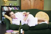 Woman Laid On Sofa Smoking And Drinking