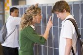 stock photo of hair integrations  - Female teacher reprimanding a male student - JPG