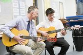Teacher Helping Teen Pupil With Guitar Lessons
