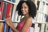 Frau in Bibliothek ziehen Buch aus einem Regal (Depth of Field)