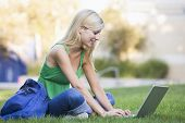 Woman Outdoors Sitting On Grass With Laptop (Selective Focus)