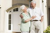 stock photo of old couple  - Senior couple standing outside their home - JPG