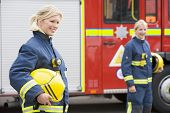 Firewomen Standing By Fire Engine With Another Firewoman In Background (Selective Focus)
