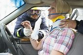 Two Firemen Helping A Woman In Neck Brace Breathe With Oxygen Mask