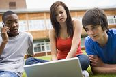 Three Students Outdoors On Lawn With Laptop One On Cellular Phone