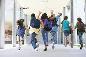 image of rear-end  - Six students running to front door of school excited - JPG