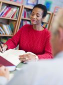 Woman Sitting Near A Man In Library With A Book And Notepad (Selective Focus)