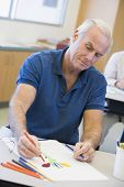 stock photo of senior-citizen  - Adult student in class drawing picture - JPG