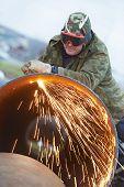 Постер, плакат: Строительный рабочий сварщика в защитных очках резки металлических труб на создание сайта с сварки fl