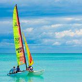 VARADERO,CUBA-NOVEMBER 3:Young couple sailing on a catamaran November 3,2012 in Varadero.With over a million visitors per year,Varadero is the destination of 40% of tourists visiting the island