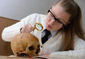 Woman examining a human skull