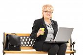 Mature professional woman with coffee cup working on a laptop and sitting on a bench isolated on whi
