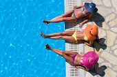 stock photo of bathing  - Three women in bikini wearing a straw hat by the swimming pool - JPG