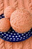 Three ball of pink yarn on talelke with asterisks