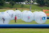 Several Kids Roll Around In Large Zorbs At Summer Festival