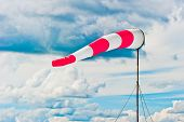 striped windsock at the airport on the background of beautiful clouds